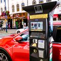 Red Car Parked Next To A Modern Parking Meter Royalty Free Stock Photo