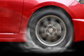 Red car racing spinning wheel burns rubber on floor. Royalty Free Stock Photo