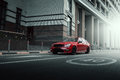 Red car stay on asphalt road in the city at daytime Royalty Free Stock Photo