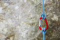 Red carabiner with climbing rope on rocky background