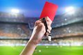 Red card hand of referee with and whistle in the soccer stadium Stock Image
