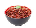 Red cargo rice a bowl of garnished with a single leaf of lemon basil shot on white background Royalty Free Stock Photo