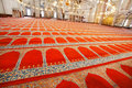 Red carpets with traditional patterns on floor of 16th century Suleymaniye Mosque with bright lights Royalty Free Stock Photo