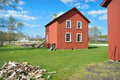 Red carriage house the historic at old world wisconsin with the st peter s church in the background there is a wood pile in the Royalty Free Stock Image