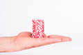 Red casino chips on human hands isolated on white Royalty Free Stock Photo