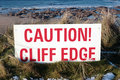 Red caution sign on slippery cliff edge Stock Photography
