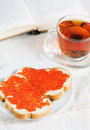 Red caviar on a slice of bread, tea and open book Royalty Free Stock Images