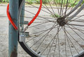 Red chain and silver colored lock on bicycle wheel. Royalty Free Stock Photo