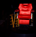 Red chair isolated vivid against black background surrounded by several stools Royalty Free Stock Images