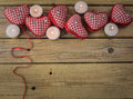 Red check hearts with candles on rustic wooden background