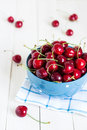 Red cherries in bowl on white wooden background on blue towel