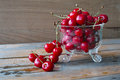 Red cherries fresh in glass bowl against wooden background Royalty Free Stock Images