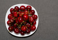 Red cherries on a plate, textured gray background, space for text Royalty Free Stock Photo