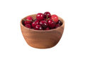 Red cherries in wooden bowl isolated on white background with cl