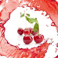 Red cherry with leaves and juice isolated on white background Royalty Free Stock Photos