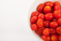 Red cherry tomatoes in a bowl on white background Royalty Free Stock Photo