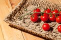Red cherry vine sun-ripened piccolo tomatoes in wicker basket tr Royalty Free Stock Photo