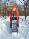 Red children's slide as a locomotive in the snow park area of ​​the city Royalty Free Stock Photo