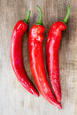 Red chili peppers over wooden background Royalty Free Stock Images