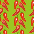 Red chilli pepper seamless pattern on green background.. Royalty Free Stock Photo