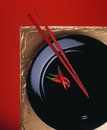 Red chillis and chopsticks on black plate Royalty Free Stock Photo