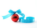 close up single red glossy christmas ball with bright blue ribbon bow isolated on white background Royalty Free Stock Photo