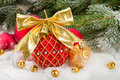 Red christmas ball with golden bow in snow under fir tree Royalty Free Stock Photos