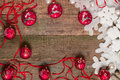 Red Christmas ball and ribbons on wooden background near white snowflake  pine. New year card. Frame. Top view. Royalty Free Stock Photo