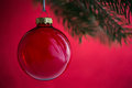 Red christmas ball on the xmas tree on red bokeh background. Merry christmas card.