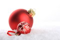 Red christmas balls with white pattern on artificial snow Stock Image