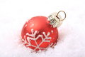 Red christmas balls with white pattern on artificial snow Royalty Free Stock Photography