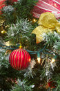 Red christmas bauble and gold ribbon in a tree with light decorations Royalty Free Stock Photo