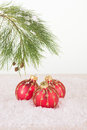 Red christmas baubles and pine tree branch in snowflakes close up Stock Photo
