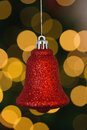 Red christmas bell decoration hanging on blurred background Stock Image