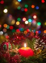 Red christmas candle a surrounded by pine branches with lights in the background and tree Royalty Free Stock Image