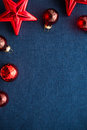 Red christmas decorations stars and balls on dark blue canvas background. Merry christmas card. Royalty Free Stock Photo