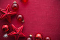 Red christmas decorations (stars and balls) on red canvas background. Merry christmas card. Royalty Free Stock Photo