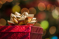 Red christmas gift box with gold bow under a tree with defocused lights Royalty Free Stock Images