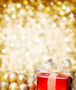 Red Christmas gift with gold baubles and golden background. Royalty Free Stock Photo
