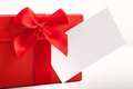 Red christmas gift tied with a ribbon and bow decorative blank white tag for your seasonal greeting or message Royalty Free Stock Photos