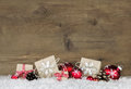 Red Christmas gifts wrapped in natural paper on old wooden grey