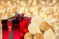 Red christmas holiday gift bright background shiny present for xmas with white and gold balls or baubles golden sparkling bokeh Stock Photography
