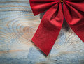 Red Christmas knot on wooden board top view celebrations concept Royalty Free Stock Photo