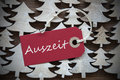 Red christmas label with auszeit means downtime ribbon on wooden trees background vintage or rustic style german text Royalty Free Stock Image