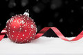 Red christmas ornament with ribbon on black Royalty Free Stock Photo