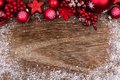 Red Christmas ornament top border with snow frame on wood Royalty Free Stock Photo