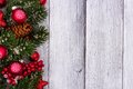 Red Christmas ornaments and branches side border on white wood Royalty Free Stock Photo