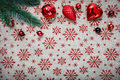 Red Christmas ornaments (cones,balls) and xmas tree on canvas background with red glitter snowflakes Royalty Free Stock Photo