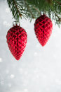 Red christmas ornaments cones on the xmas tree on glitter bokeh background.