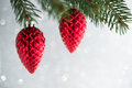 Red christmas ornaments cones on the xmas tree on glitter bokeh background. Merry christmas card.